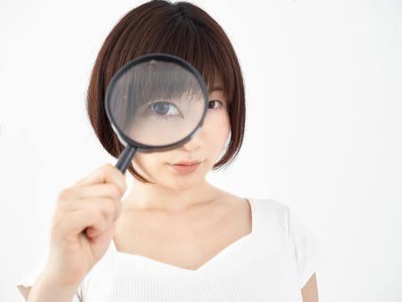 虫眼鏡を覗き込む女性
