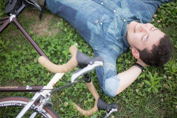 自転車と寝転ぶ男性
