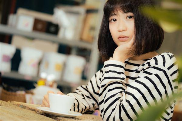 コーヒーカップを持つアンニュイな表情の女性