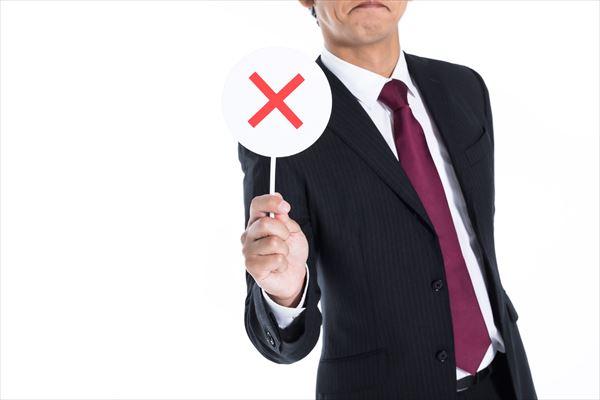 バツマークを掲げるスーツ姿の男性
